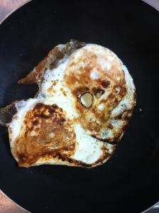 Burnt eggs in a frying pan