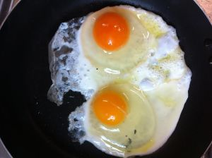 A frying pan with two eggs in it being fried