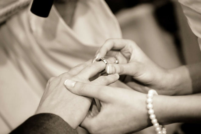 A Bride putting a wedding ring on a Groom's finger in black and white