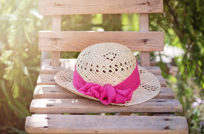 A hat on a chair with a pink ribbon in the sun